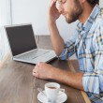 Casual man using laptop having coffee — Stock Photo #53926515