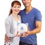 Couple holding a white piggy bank — Stock Photo #53926733