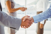 Two fellow employees shaking hands — Stock Photo