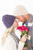 Attractive couple in warm clothing holding flowers — Stock Photo