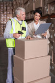 Warehouse worker scanning box with manager — Stock Photo