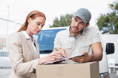 Delivery driver showing where to sign to customer — Stock Photo