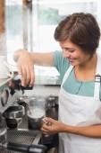Pretty barista steaming jug of milk at coffee machine — Stock Photo