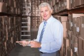Smiling warehouse manager writing on clipboard — Stock fotografie