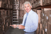 Smiling warehouse manager writing on clipboard — Stockfoto