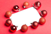 White page surrounded by christmas baubles — ストック写真
