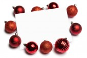 Red christmas baubles surrounding white page — 图库照片