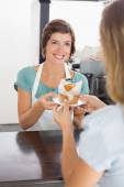 Pretty waitress serving muffin to customer — Stok fotoğraf