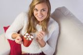 Pretty blonde enjoying hot chocolate on the couch — Stock Photo
