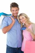 Attractive young couple with shopping bags and credit card — Stock Photo