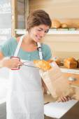 Pretty waitress putting croissant in paper bag — Stockfoto