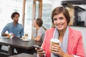 Pretty brunette sending a text drinking coffee — Stock Photo
