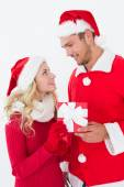 Attractive young couple wearing santa hats with gift — Foto de Stock