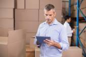 Warehouse manager using his tablet pc — Stock Photo