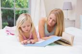 Girl and mother on bed reading — Foto Stock
