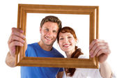 Couple holding frame ahead of them — Stock Photo
