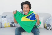 Brazilian football fan cheering while watching tv — Stock Photo