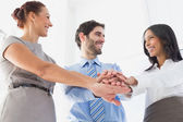 Workers with stacked hands smiling — Stock Photo