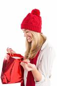 Happy blonde opening gift bag  — Stock Photo