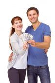 Couple holding fan of cash — Stock Photo