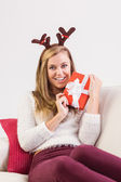 Festive blonde relaxing on sofa with gift — Stock Photo