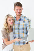 Portrait of happy young couple using laptop — Foto Stock