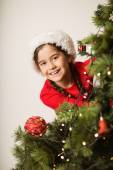 Festive little girl hanging a christmas decoration — Stock fotografie