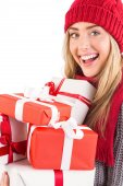 Festive blonde holding pile of gifts — Stockfoto