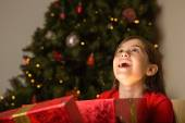 Little girl opening a magical christmas gift — Stockfoto