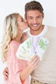 Woman kissing man as she holds banknotes — Foto Stock