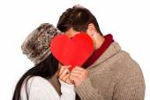 Young couple kissing behind red heart — Stock Photo