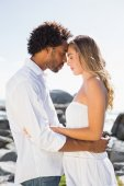 Gorgeous couple embracing by the coast — Foto Stock