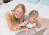 Girl and mother on bed using laptop — ストック写真
