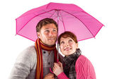 Couple standing underneath an umbrella — ストック写真