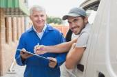 Delivery driver showing customer where to sign — Stock Photo