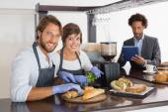 Happy servers preparing sandwiches together — Stock fotografie