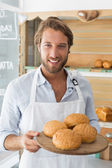 Handsome waiter holding tray of bread rolls — Stock Photo