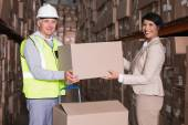 Warehouse worker and manager passing box — Stock Photo