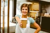 Pretty barista smiling at camera holding disposable cup — Stock Photo