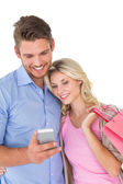 Happy young couple looking at mobile phone — Stock Photo