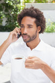 Smiling man on the phone having coffee — Stock Photo