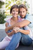Happy couple sitting and cuddling — Stock Photo