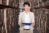 Pretty warehouse manager holding tablet pc — Photo