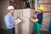Warehouse worker loading up pallet with manager — Stock Photo