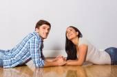 Young couple lying on floor smiling — Stock Photo