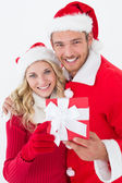 Attractive young couple wearing santa hats with gift — 图库照片