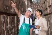 Warehouse worker and manager using tablet — Stock Photo
