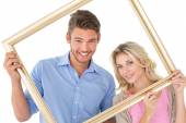 Attractive couple smiling at camera through picture frame — Stockfoto