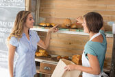 Pretty waitress serving roll to customer — Stockfoto
