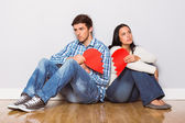 Young couple sitting on floor with broken heart — Stock Photo